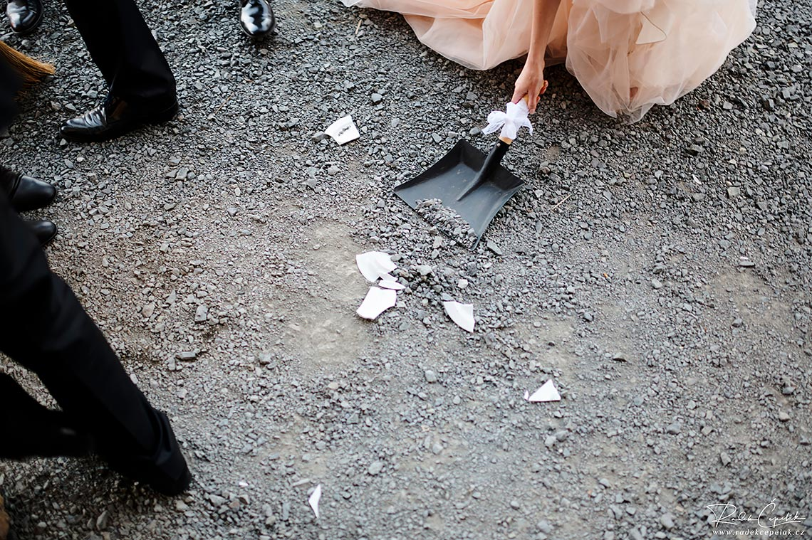 bride and groom cleaning the shards from broken plate