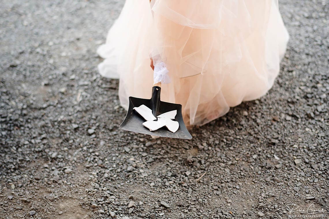 bride holding dustpan with shards