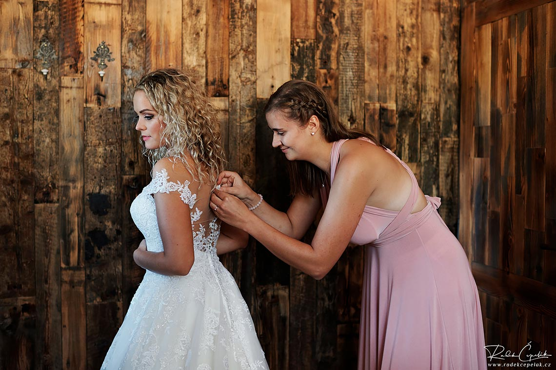 buttoning wedding dress of bride before going to ceremony