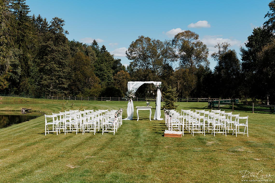 white chairs on outside wedding ceremony