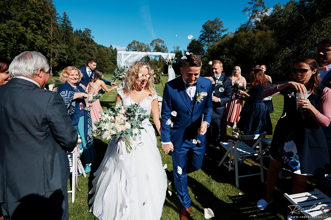 Newlyweds leaving ceremony place after marriage on the aisle between guests