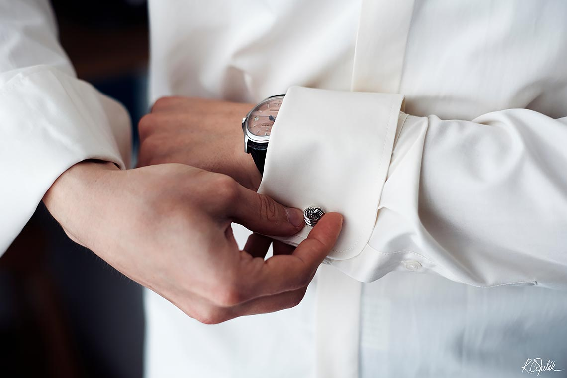 groom buttoning the cufflinks