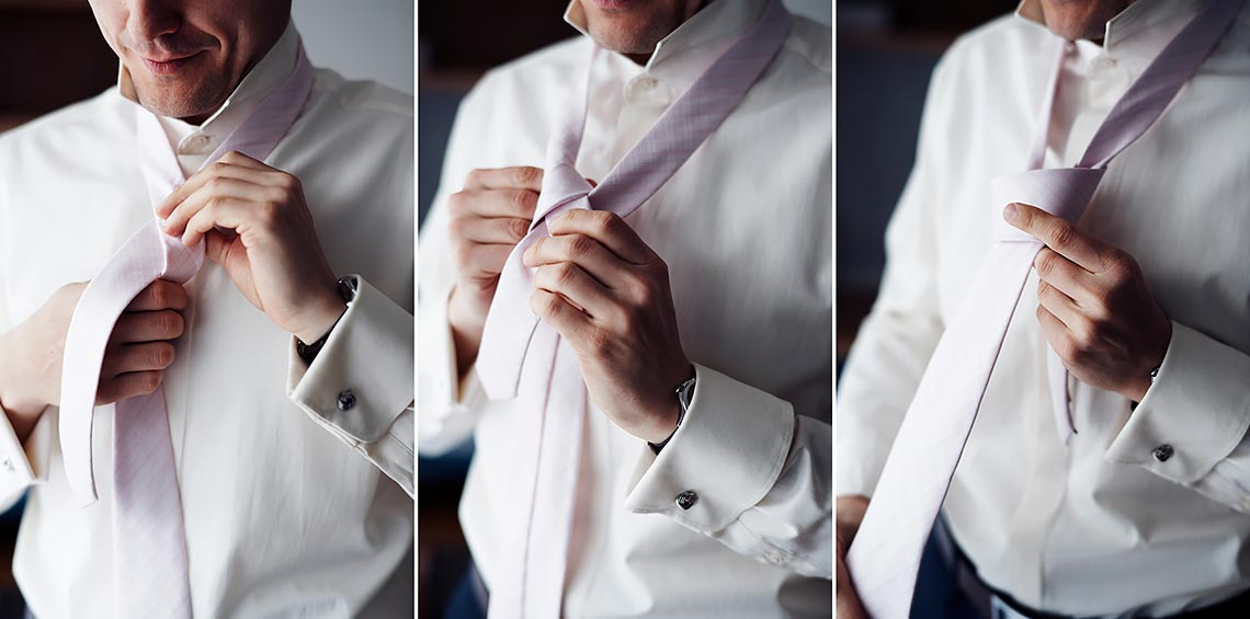 groom tieing his tie