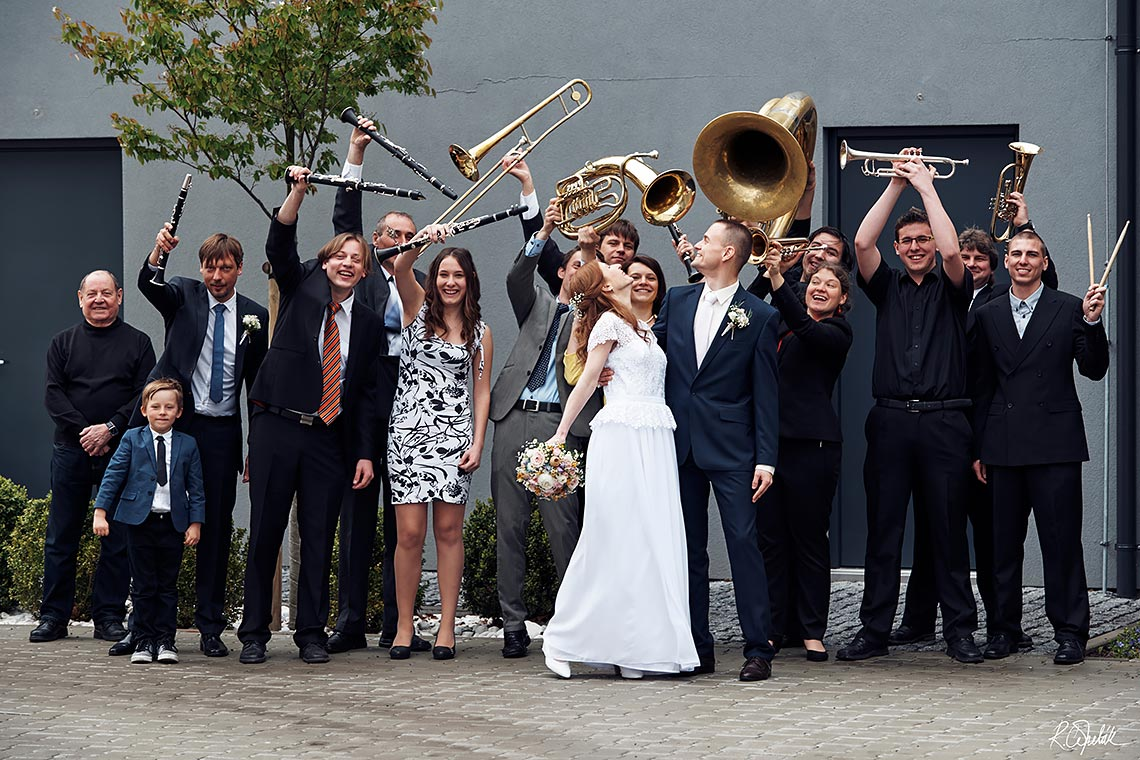 group photo of bride and groom with breathing orchestra