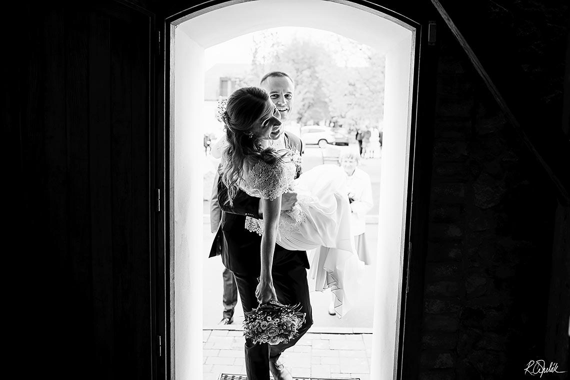 groom holding her bride in hands crossing doorsill