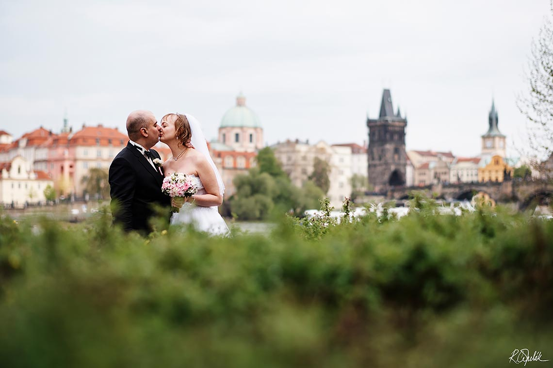 kissing bride and groom with Prague at background