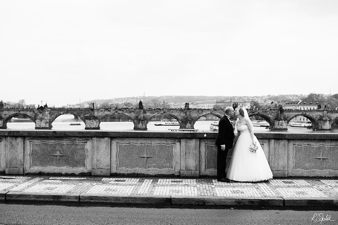 kissing bride and groom black and white photo