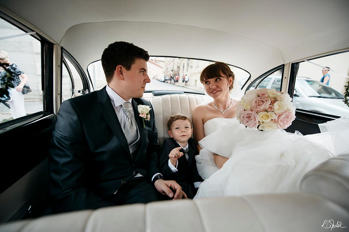 moment of smiling bride sitting into the vintage car
